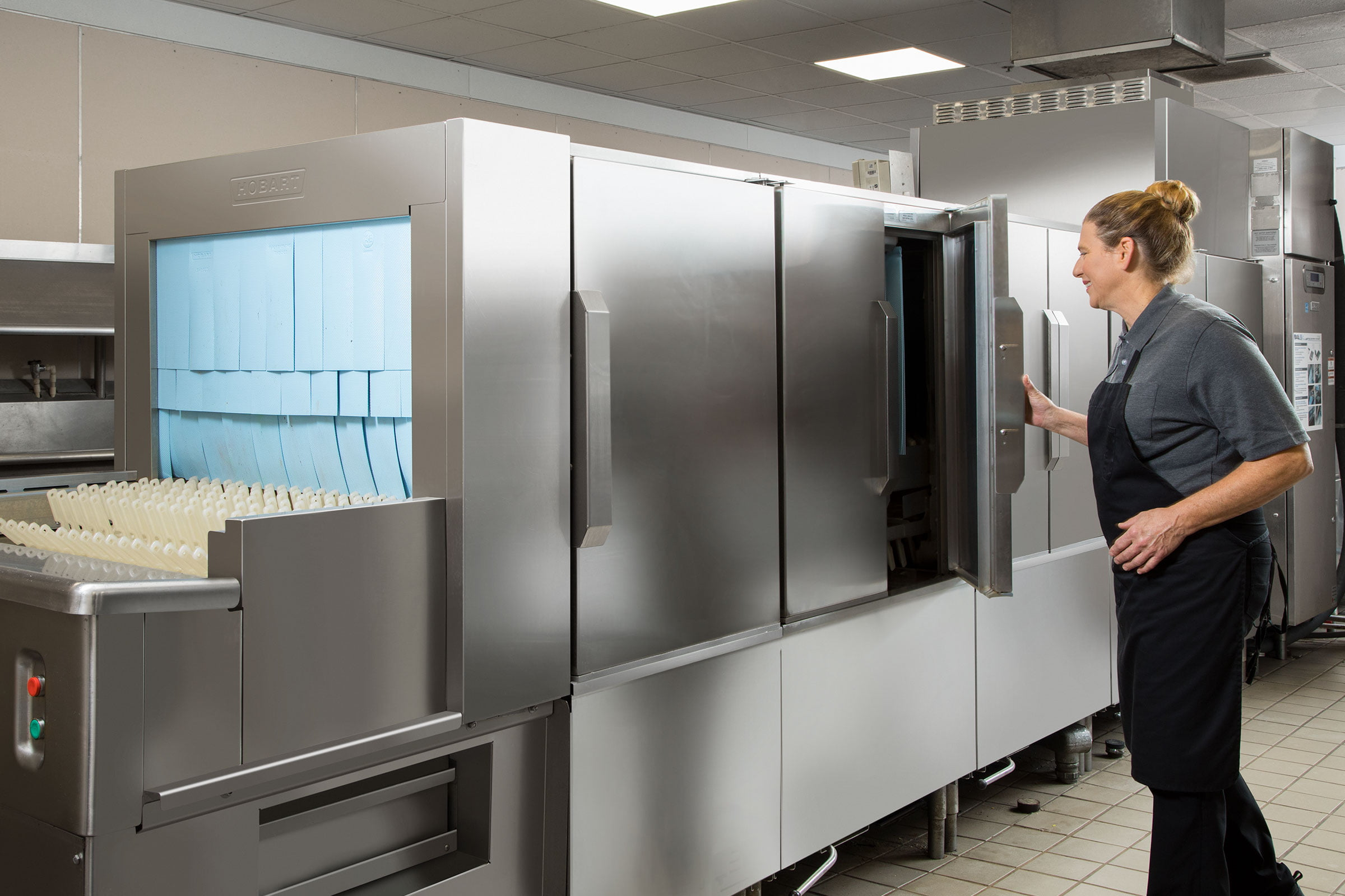 Worker Opening The FT1000e Flight Type Commercial Dishwasher