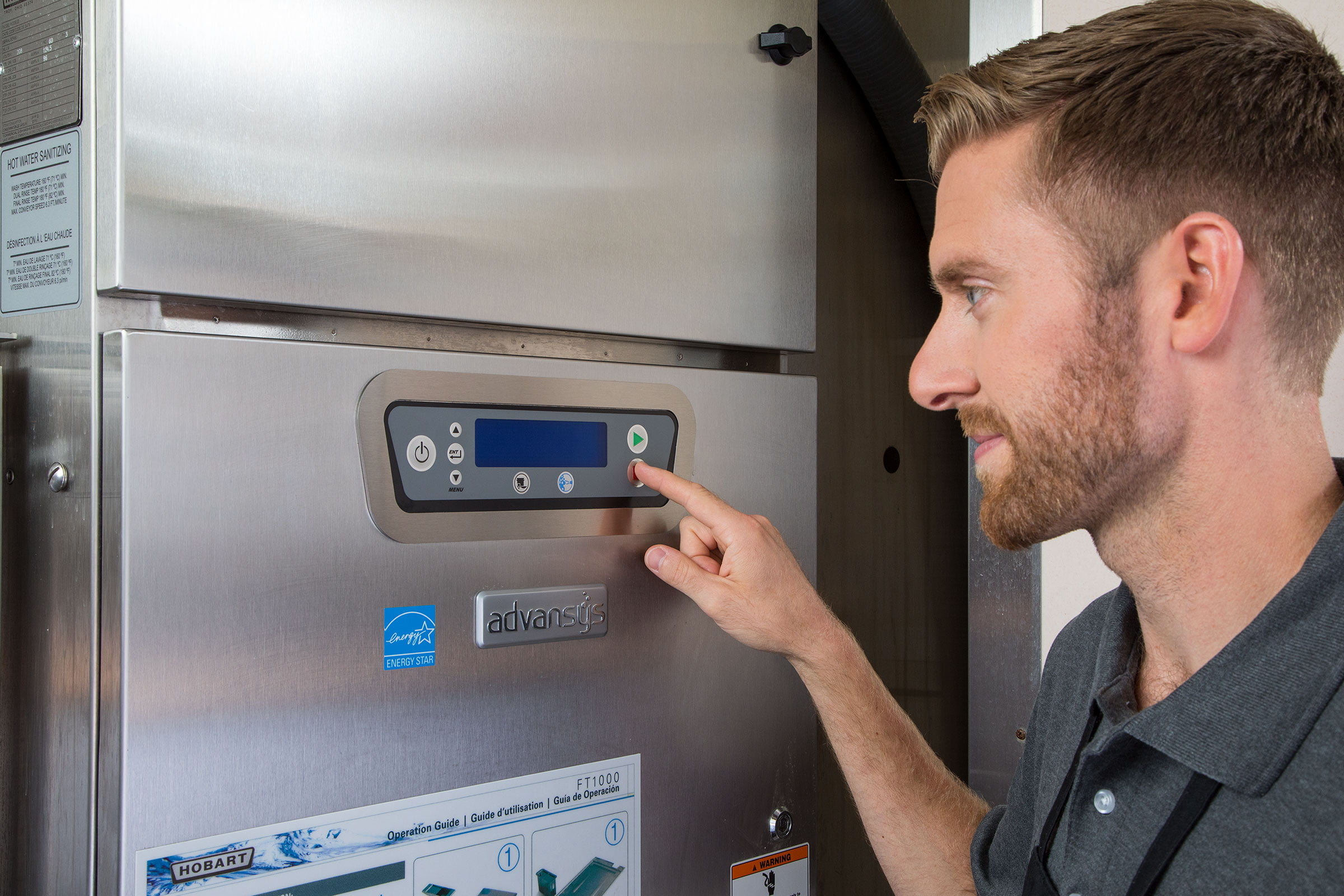 Worker Configuring FT1000e Flight Type Commercial Dishwasher